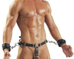Man with a leather cock ring thong on, with his wrist cuffed to the thong.
